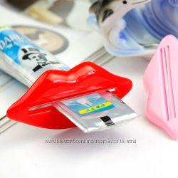 Набор выдавливателей для зубной пасты и кремов в виде губ двух цветов.